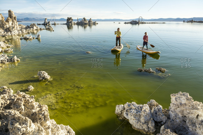 A woman and her daughter stand up paddleboarding on Mono Lake,  Lee Vining, California