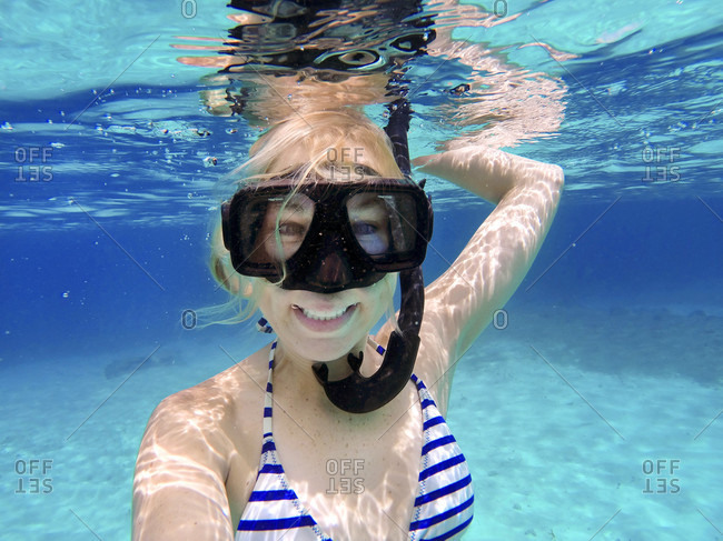 Woman underwater smiling, looking at the camera, with a snorkel mask on