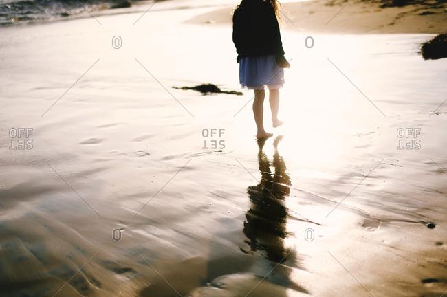 Girl walking on sunlit sand