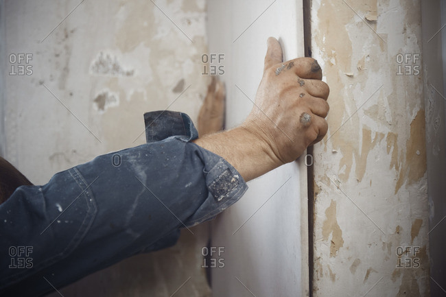 Hands of construction man hanging drywall
