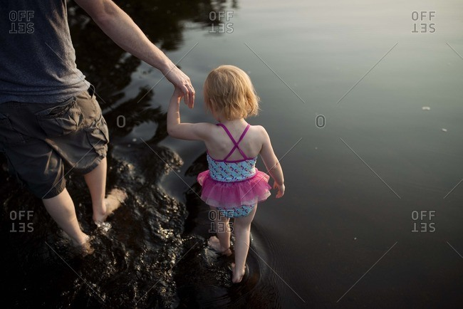 Man holding girl's hand in water