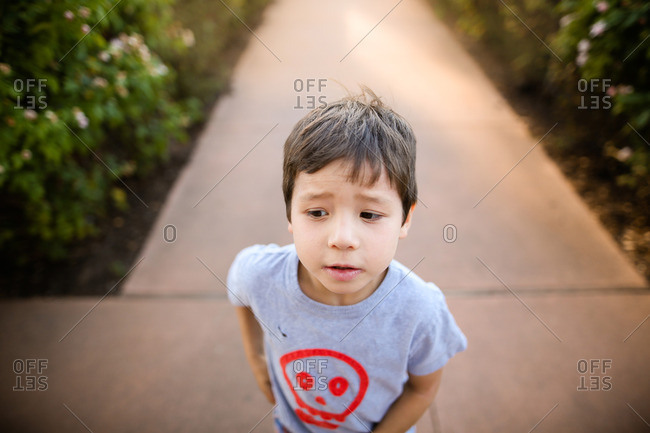 Young boy standing outside on a sidewalk