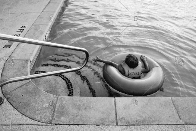 Boy floating in a life ring near the steps of a swimming pool