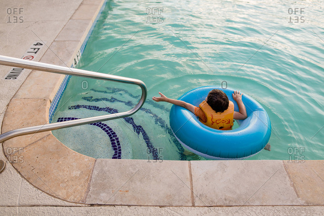 Boy floating in a life ring near the steps of a pool