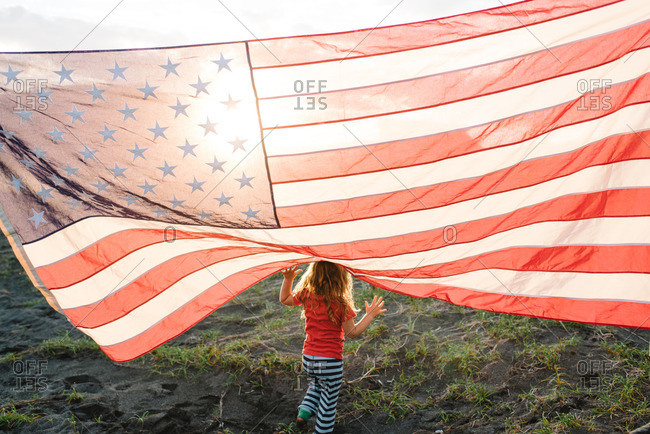 Toddler girl playing under American flag at dusk