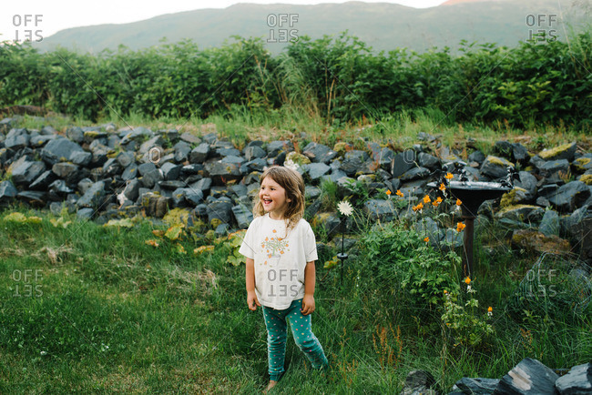 Young girl playing in garden by rock wall