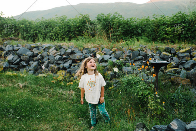 Happy toddler girl playing in garden by rock wall