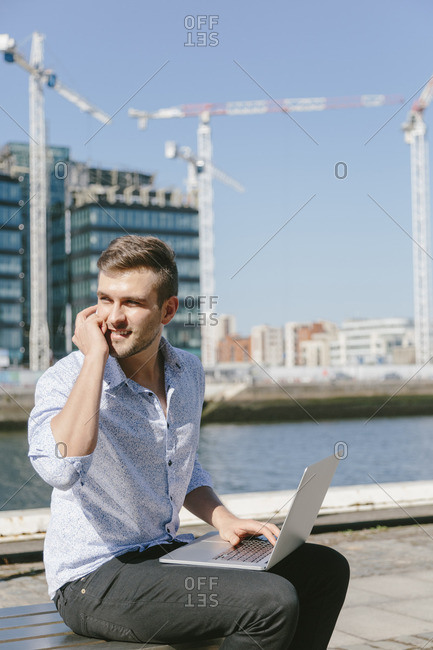 Ireland, Dublin, smiling young businessman sitting on bench with laptop telephoning with cell phone