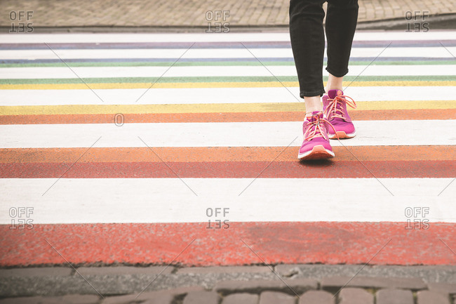 Woman crossing multi colored zebra crossing, partial view