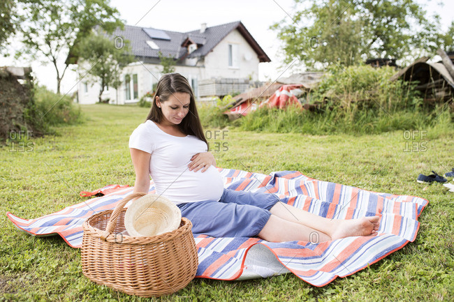 Pregnant woman sitting on picnic blanket touching her belly