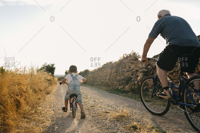Back view of little boy and his great, grandfather on bicycle tour