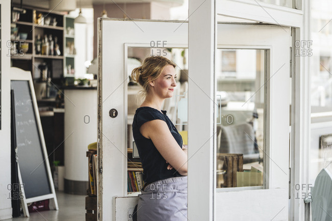 Smiling woman in a cafe looking out of window