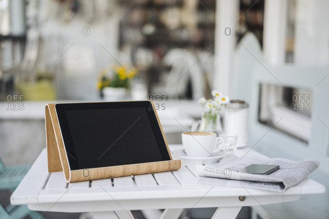 Digital tablet, cell phone, newspaper and cup of coffee on table in a cafe