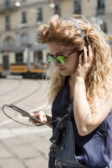 Young woman with headphones and mirrored sunglasses looking at her smartphone