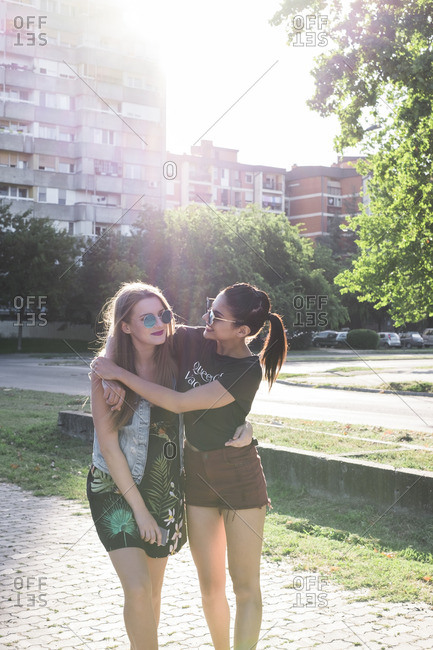 Two female friends standing at backlight