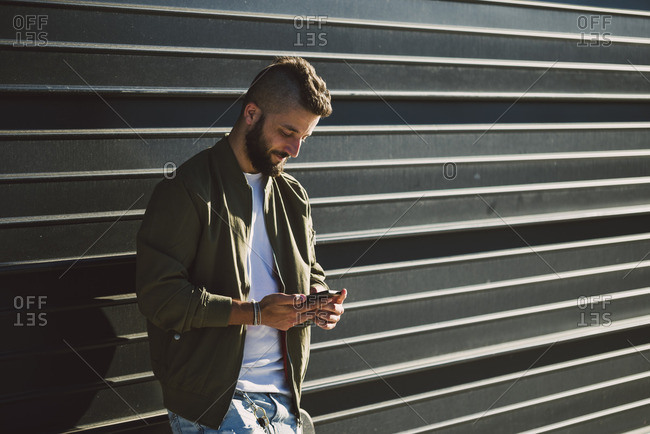 Smiling man standing in front of facade looking at cell phone
