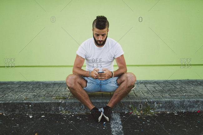 Man sitting on his skateboard at carb text messaging