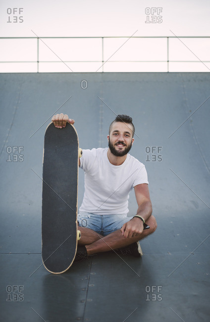Smiling skateboarder sitting on ramp in a skate park