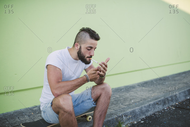 Young man sitting on skateboard, lighting a cigarette