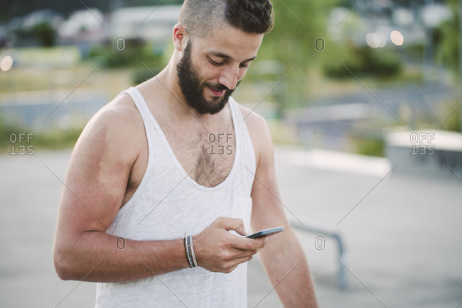 Young man with shaved head looking at cell phone