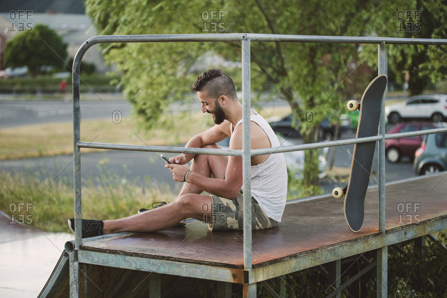Smiling skateboarder using his smartphone in a skate park