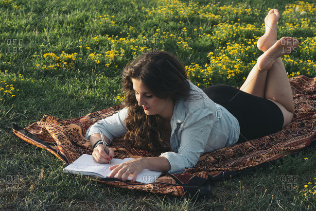 Young woman lying on blanket on a meadow writing down something in her diary
