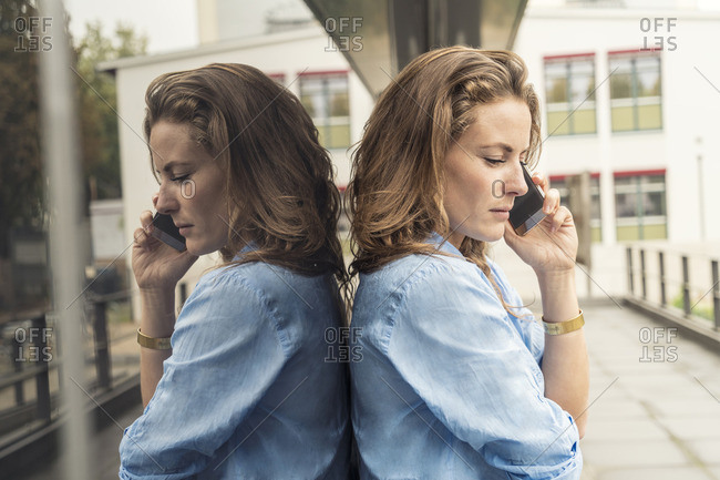 Telephoning blond woman and her mirror image on glass pane
