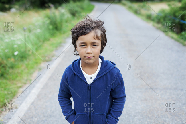 Portrait of little boy standing on a country road