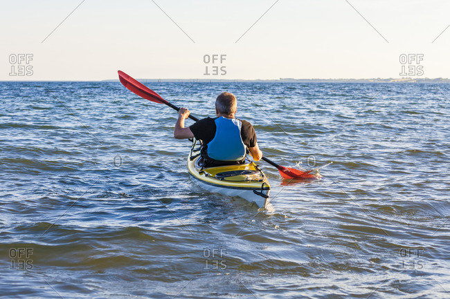 Denmark, senior man paddling, kayak