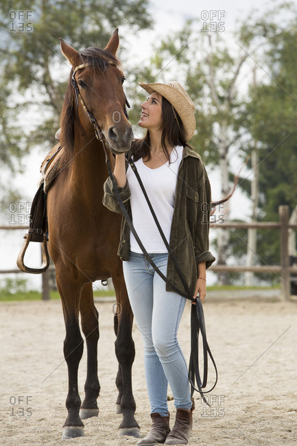 Young woman with horse at riding stable