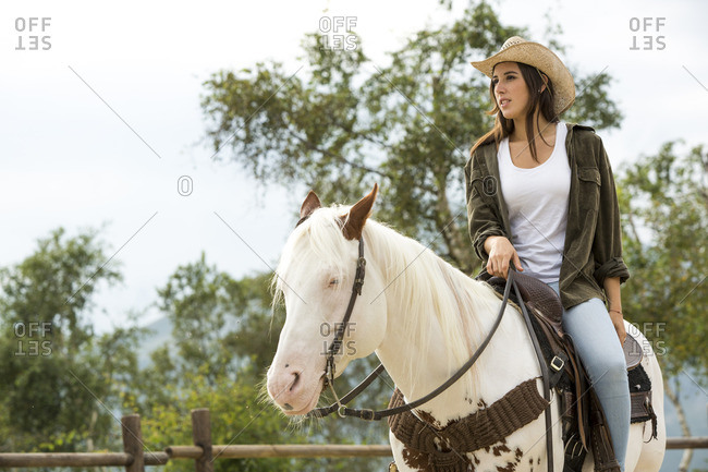 Young woman riding horse at riding stable