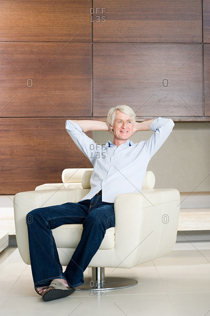 Middle aged man relaxing in modern armchair