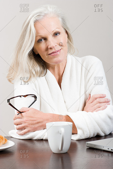Middle aged woman sitting at breakfast table in bathrobe
