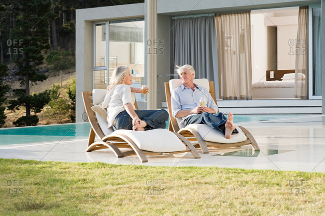 Middle aged couple relaxing on deck chairs by the pool