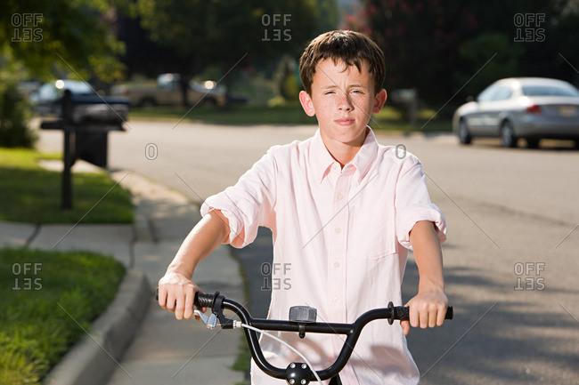 Boy with bicycle in suburban setting