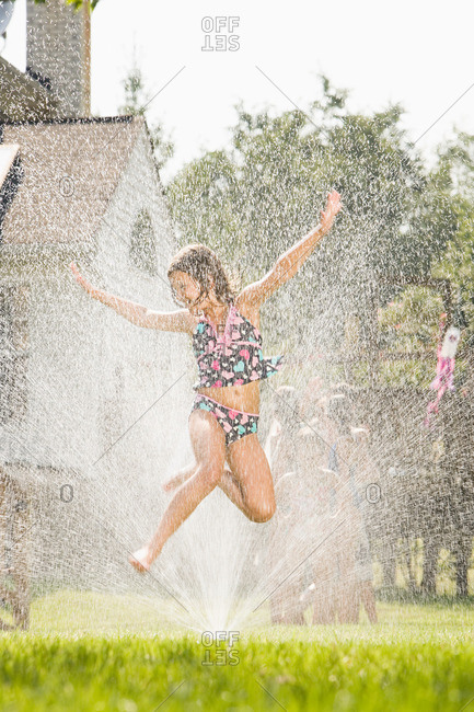 Girl jumping in sprinkler