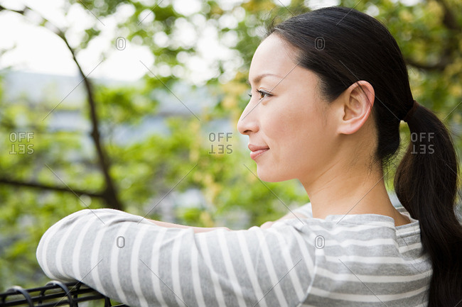 Japanese woman leaning near trees