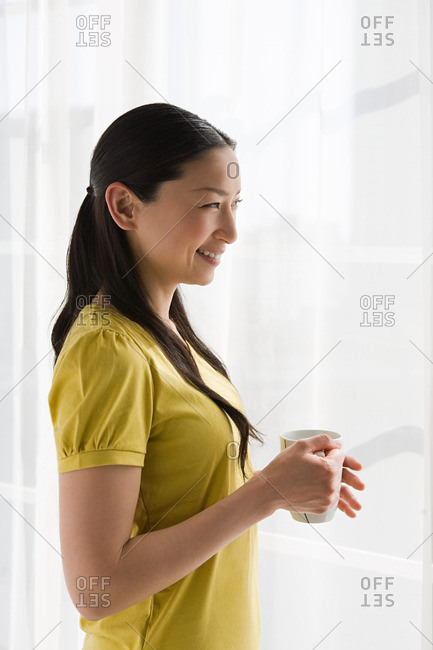 Smiling Japanese woman standing at window