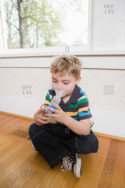 Boy using asthma inhaler with spacer