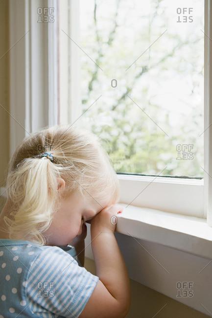 Sad little girl by window