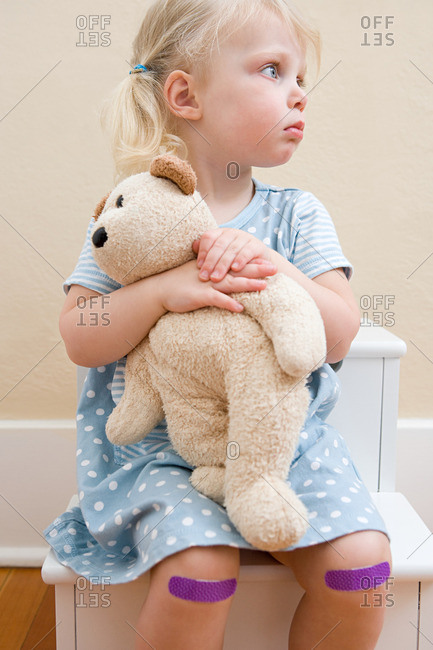 Girl with teddy bear and plasters on knees