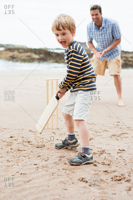 Father and son playing cricket on beach