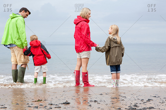 Family standing in the sea