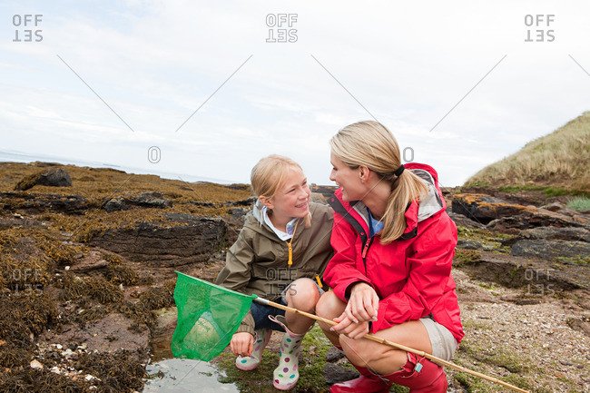 Mother and daughter by rock pools
