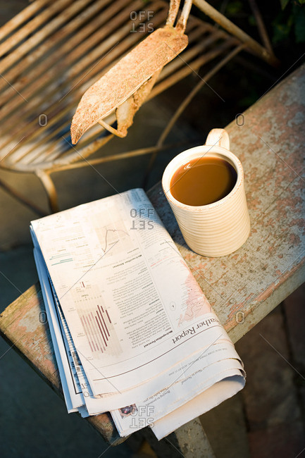 Coffee cup and newspaper outdoors