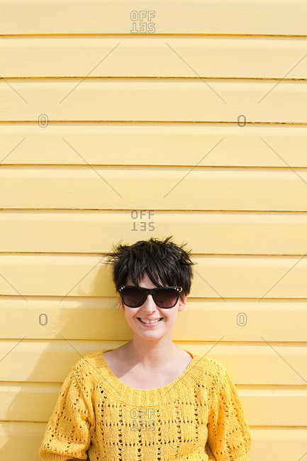 Young woman and yellow wall
