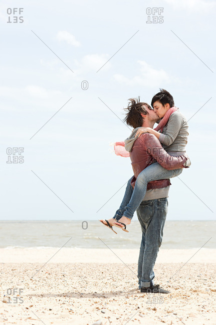 Man carrying girlfriend by the sea