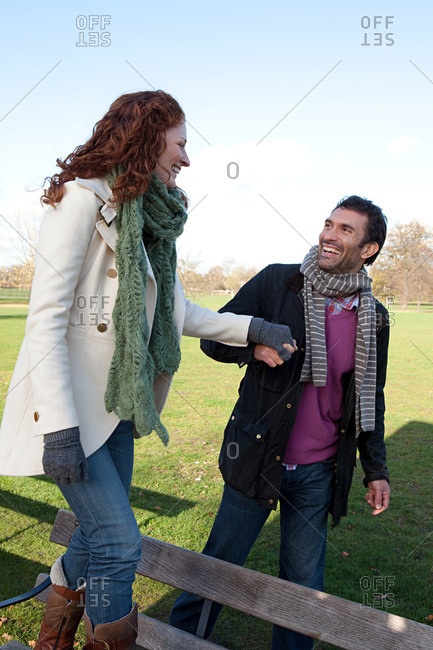 A woman walking on a park bench whilst holding hands with her partner