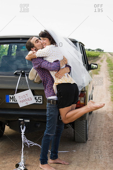 Newlywed couple by vehicle