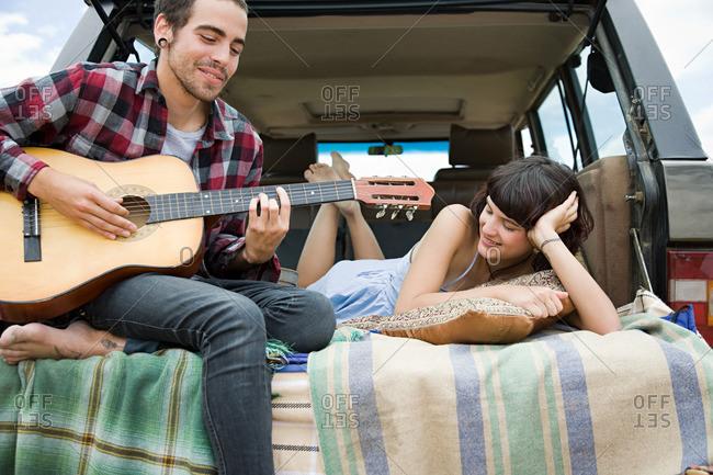 Young man playing guitar to girlfriend